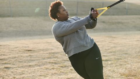 TRX Home2 System suspension trainer review: A woman in a grey workout sweater trains her upper body outside