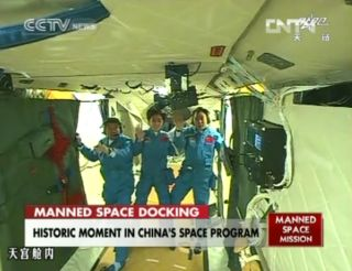 The crew of China's Shenzhou 9 mission waves to a camera aboard the Tiangong 1 space module after successfully docking their capsule at the test module on June 18, 2012.