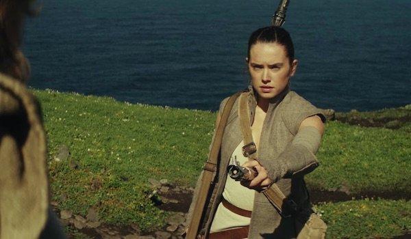 Rey handing lightsaber to Luke Skywalker