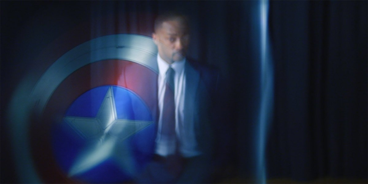 Anthony Mackie as Sam Wilson standing in the reflection of Captain America's shield in The Falcon And The Winter Soldier