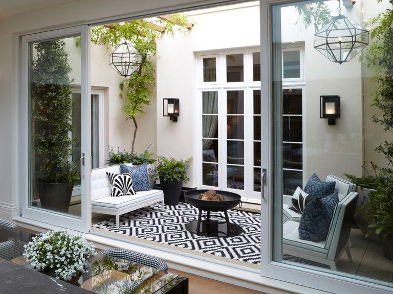 courtyard garden ideas - outdoor living room with rug and outdoor lighting