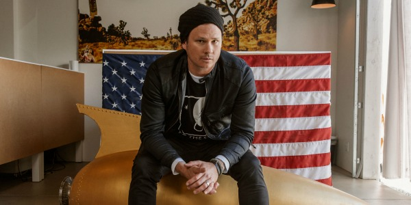 Tom DeLonge sat in front of an American flag