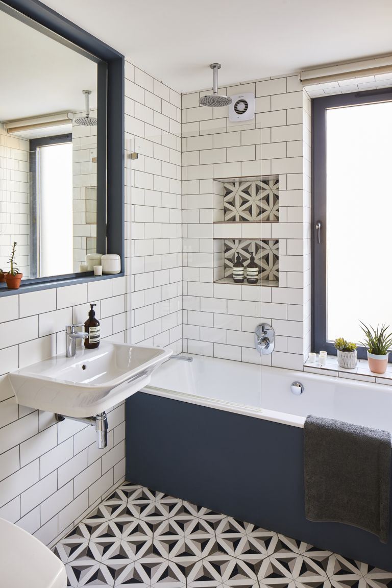 A family bathroom with white metro wall tiles, monochrome patterned floor tiles and a bath-shower with painted deep blue panel