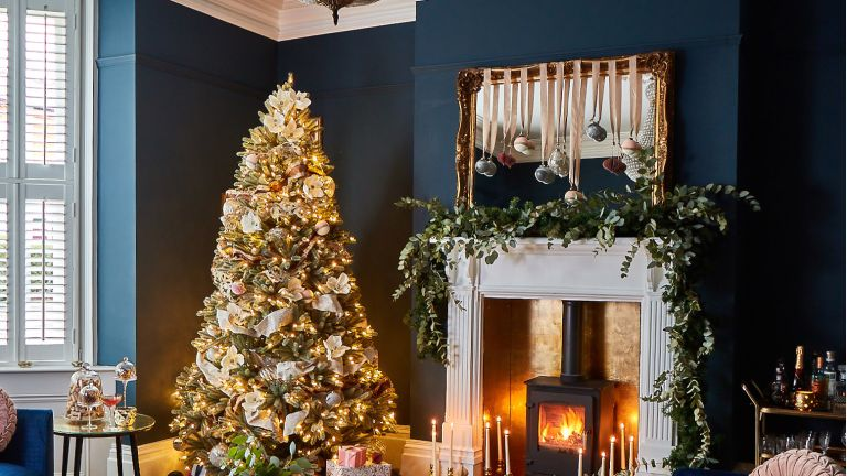 Christmas living room with a Christmas tree and a mantelpiece with a large garland