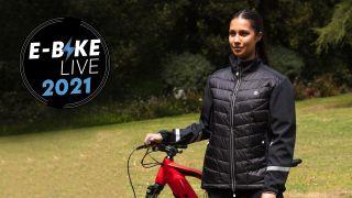 Woman wearing new Proviz ebike jacket stands next to a mountain bike