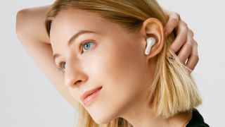 A woman pulling back her hair to show the LG Tone Free FP8 earbud in white in her left ear