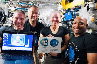 """Crew-1 astronauts Mike Hopkins, Soichi Noguchi, Shannon Walker and Victor Glover connect with Skylab 4 science pilot Ed Gibson (on screen) to mark their SpaceX Dragon """"Resilience"""" overtaking his command module's 84 days for the U.S. flight record."""