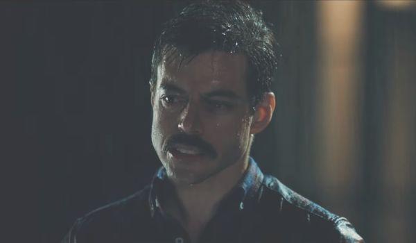 Rami Malek as Freddie Mercury standing in the rain