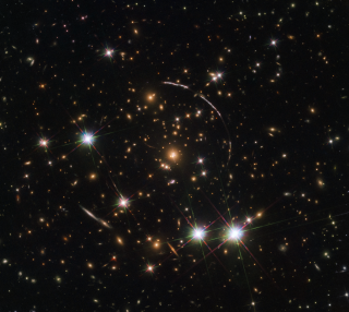 """When the Hubble Space Telescope turned its gaze toward the remote galaxy known as the """"Sunburst Arc,"""" it saw not one but 12 separate images of the lone cosmic object. That's because there's a massive galaxy cluster in the foreground warping the light with its intense gravitational pull. This illusion is known as gravitational lensing, a phenomenon that Albert Einstein first described in his theory of general relativity. """"This 'funhouse mirror' effect not only stretches the background galaxy image, but also creates multiple images of the same galaxy,"""" NASA officials said in a statement."""