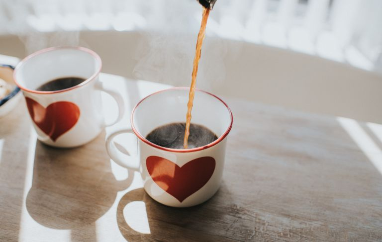Pouring black coffee into coffee cups with heart design Space for copy Conceptual