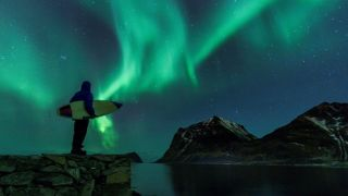 A surfer carrying a surfboard gazes at the aurora light show in the sky