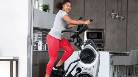 Bowflex Max Trainer M6 review: A woman in a grey sports t-shirt and red capri leggings exercises on the cross-trainer