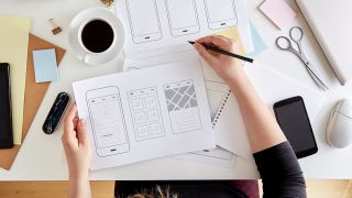 best wireframe tools: image of a woman at a desk sketching a wireframe