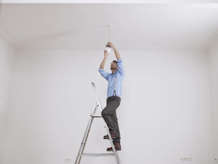man changing a ceiling light fixture
