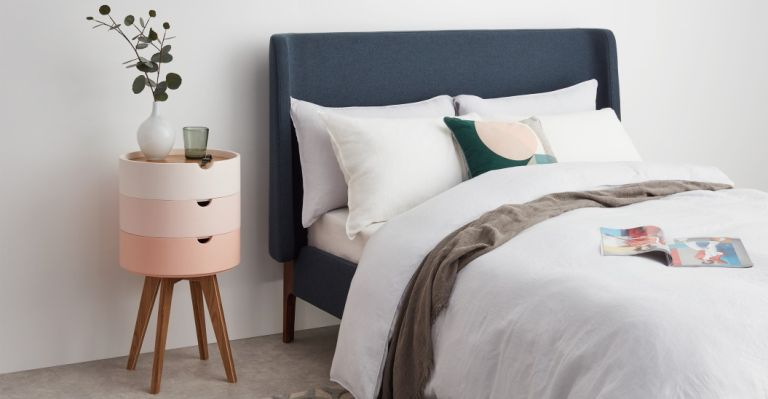 Scandinavian furniture in a bedroom with a navy bed and pink modular bedside table