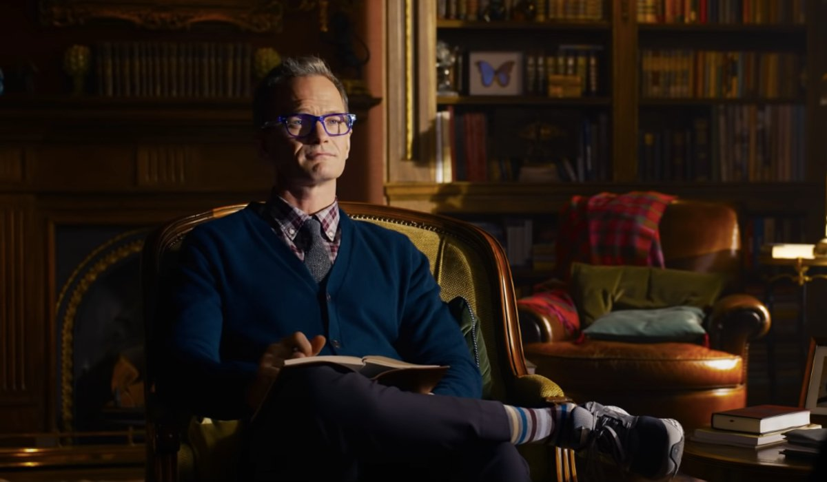 Neil Patrick Harris sits in his office taking notes in The Matrix Resurrections.
