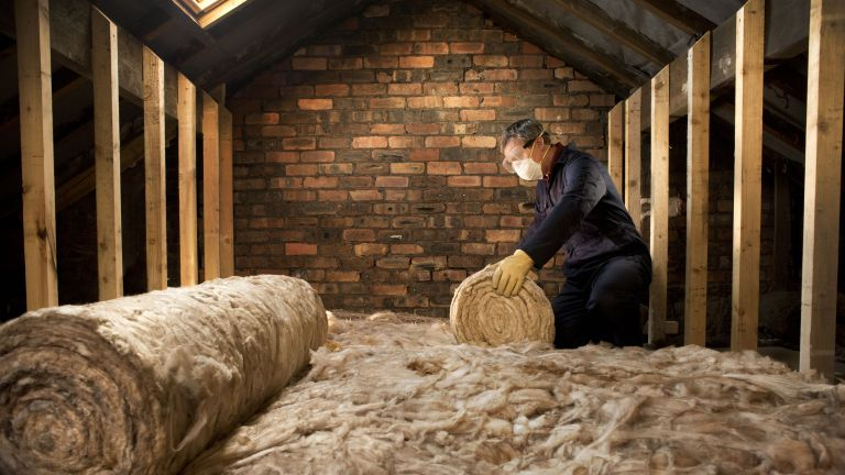 Man rolling out insulation in loft