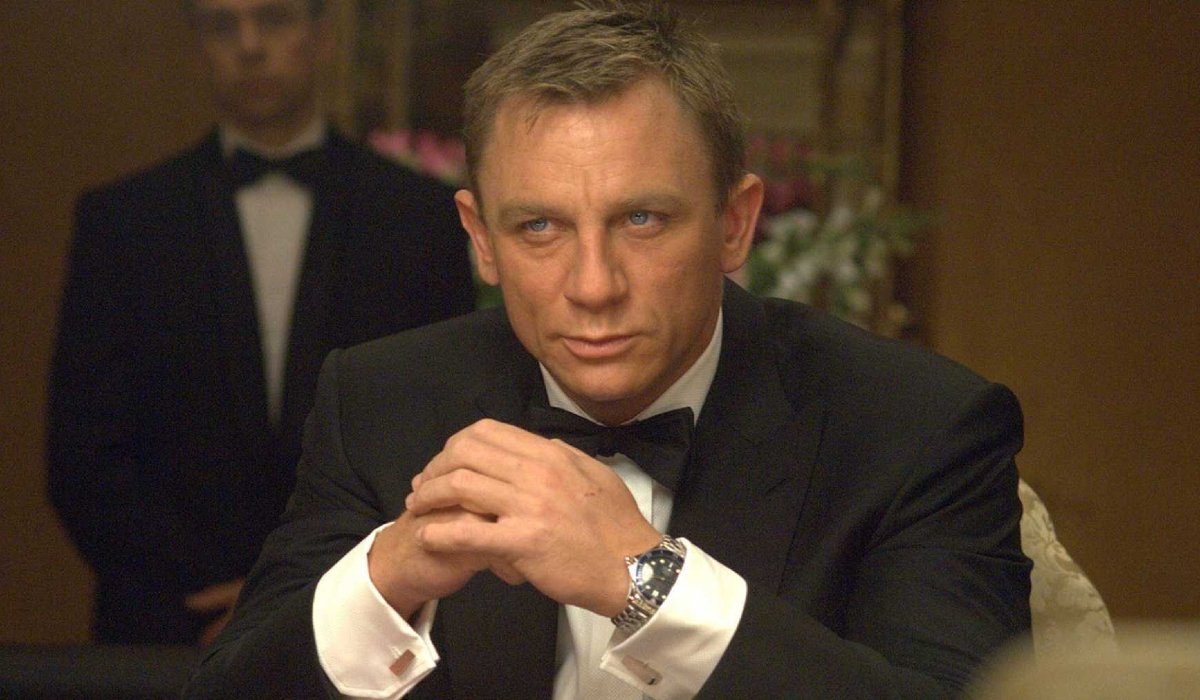 Casino Royale Bond sits smiling at the card table in his tuxedo