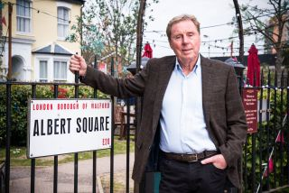 Football legend Harry Redknapp standing by the Albert Square sign in EastEnders