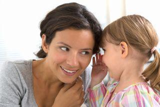 A mom listens as her daughter tells a secret.