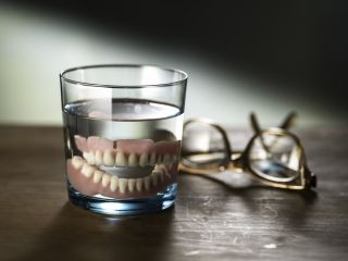 Still photograph of dentures in a glass of water.