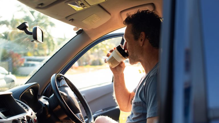 Man having his morning coffee on the move after waking up at 5am