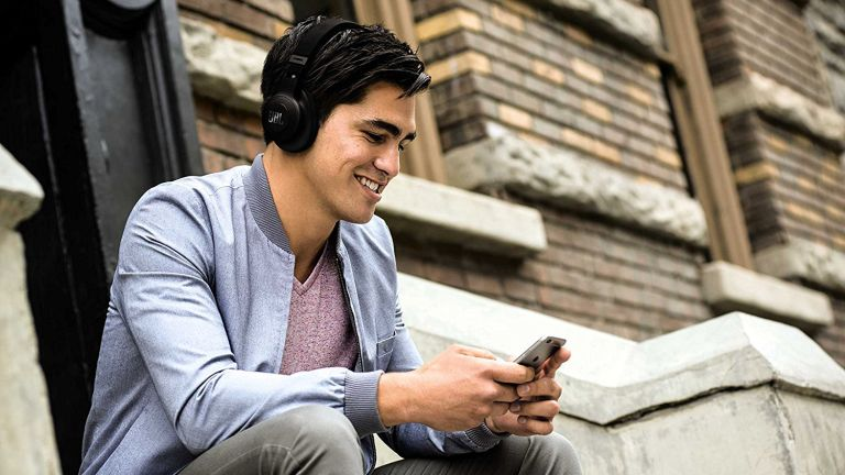 Man wearing headphones on the street, holding phone and smiling