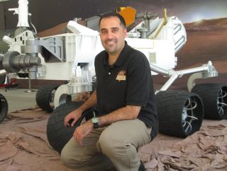 Ashwin Vasavada, the newly announced program scientist for NASA's Mars Science Laboratory mission. A full-scale model of the Curiosity rover flanks him.