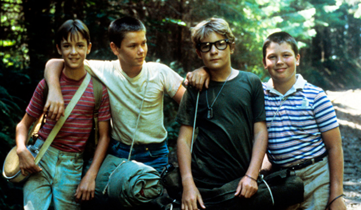 Wil Wheaton, River Phoenix, Corey Feldman, and Jerry O'Connell stand together in the woods in Stand By Me.