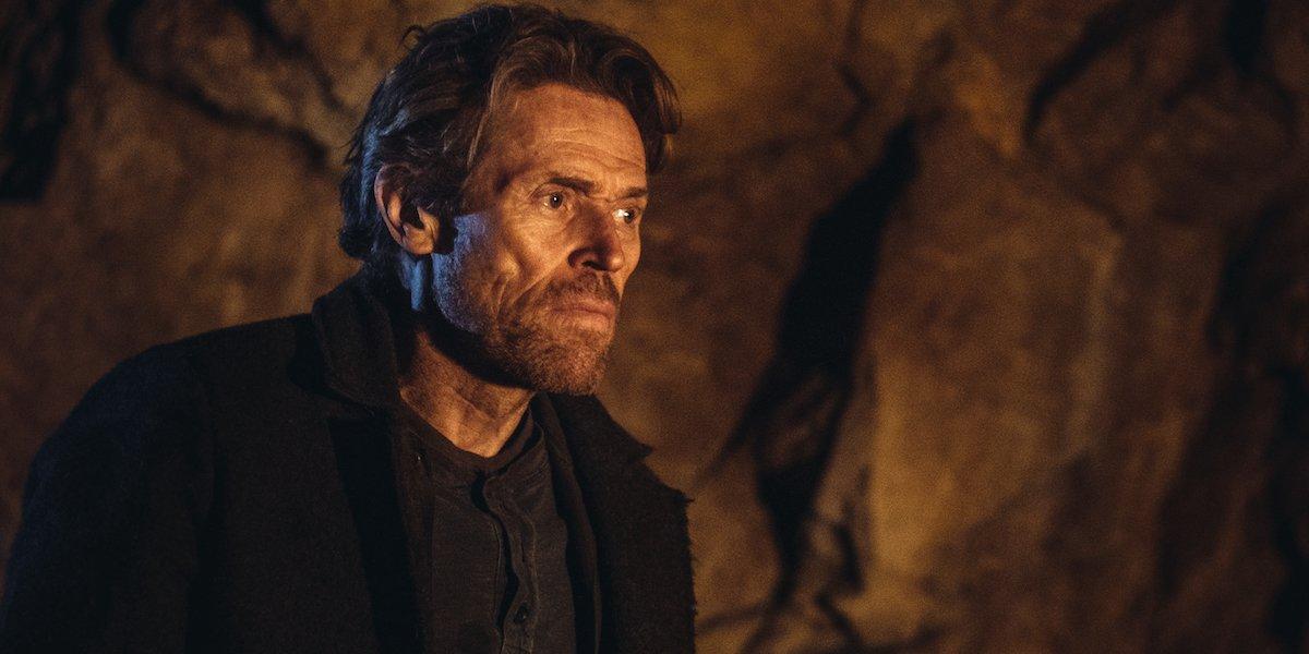 Willem Dafoe in a cave, dressed in all black