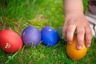 A child's hand reaches out to grab an Easter egg