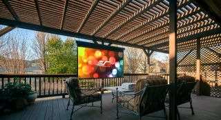 Elite Screens Yard Master Electric Projector Screen installed on a patio
