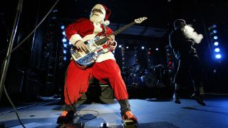 a photograph of flea dressed up as father christmas playing bass on stage