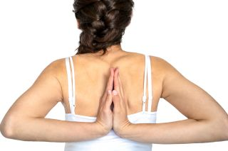 A woman with Ehlers-Danlos syndrome has the palms of her hands touching and pointed up, behind her back, between her shoulder blades.