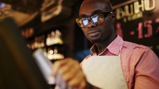 man using a pos system in a bar