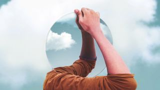 Photoshop image showing a person holding a mirror in front of their head, reflecting the sky