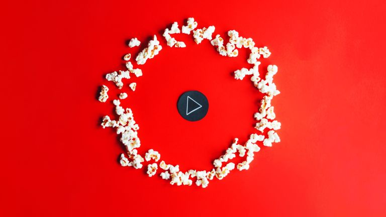 Play button and popcorn on a red background