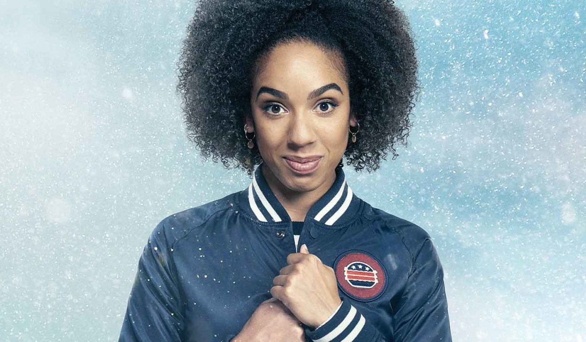 Doctor Who Bill Potts holds her jacket closed in the snow