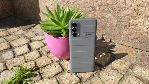 Das Realme GT Master Edition angelehnt an einen Blumentopf im Freien.