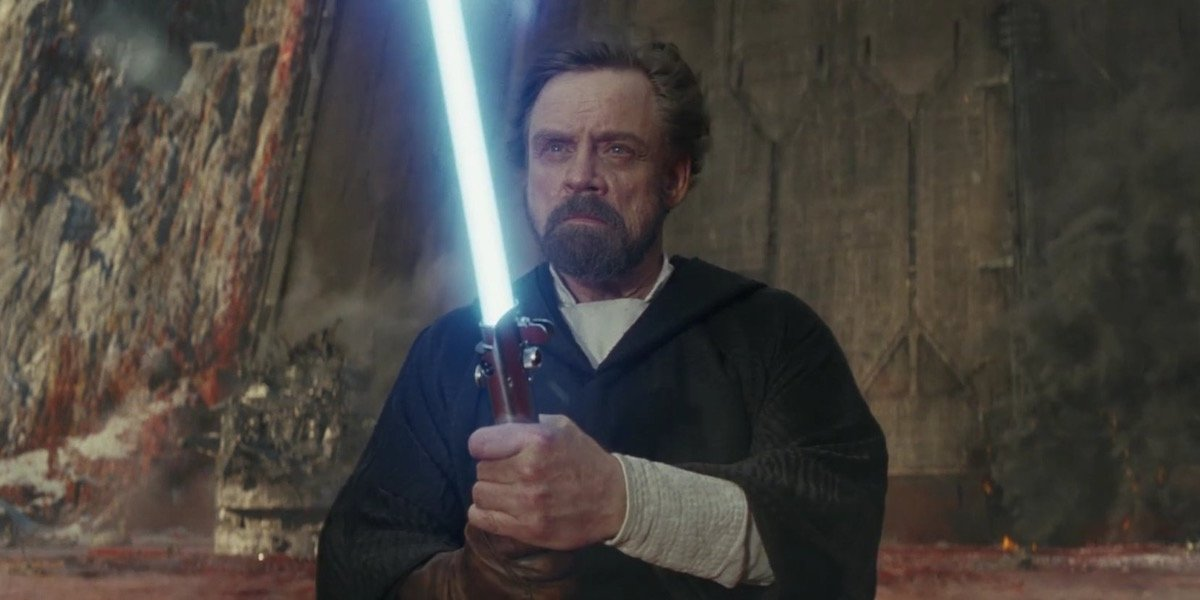 Luke Skywalker holding blue lightsaber in Star Wars: The Last Jedi