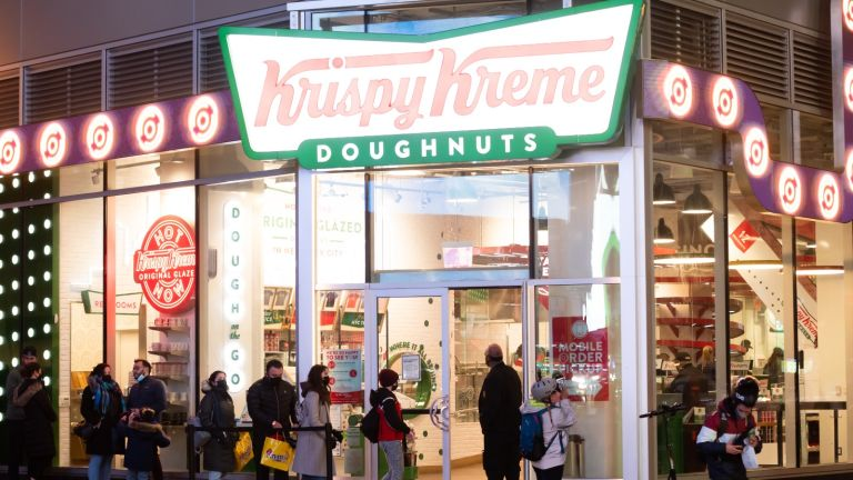 People line up outside Krispy Kreme in Times Square amid the coronavirus pandemic on March 17, 2021 in New York City.