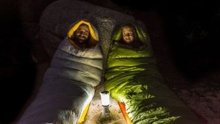 best camping lantern: couple in sleeping bags with lantern