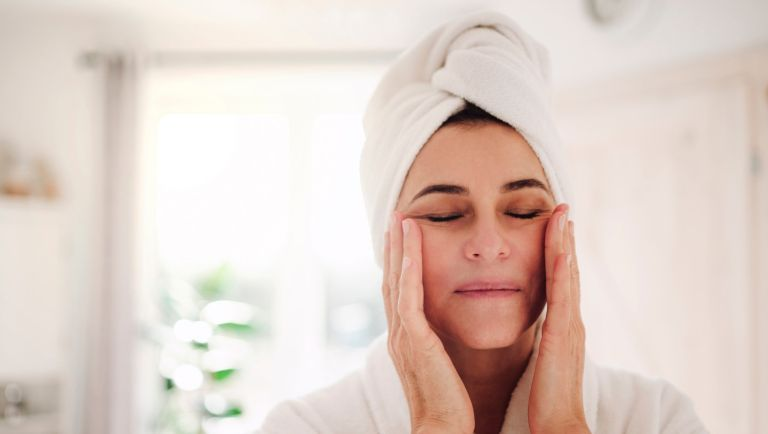 Portrait of mature woman in a bathroom at home applying moisturizer - stock photo