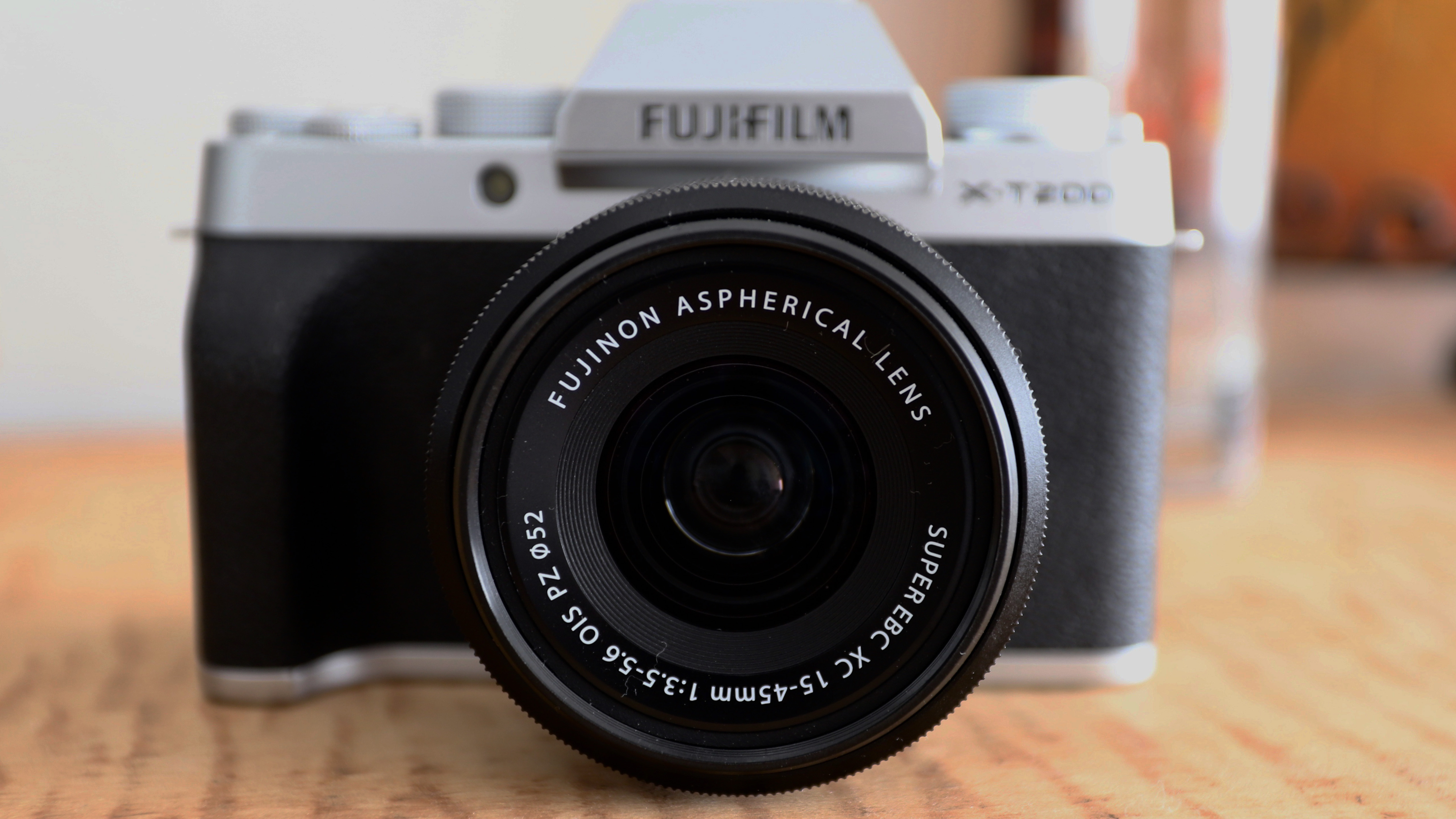 The Fujifilm X-T200 sat on a wooden table with its 15-45mm kit lens