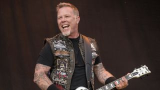 James Hetfield playing guitar onstage and smiling