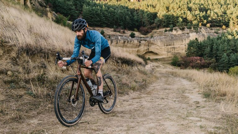 Man riding gravel bike in a hilly landscape
