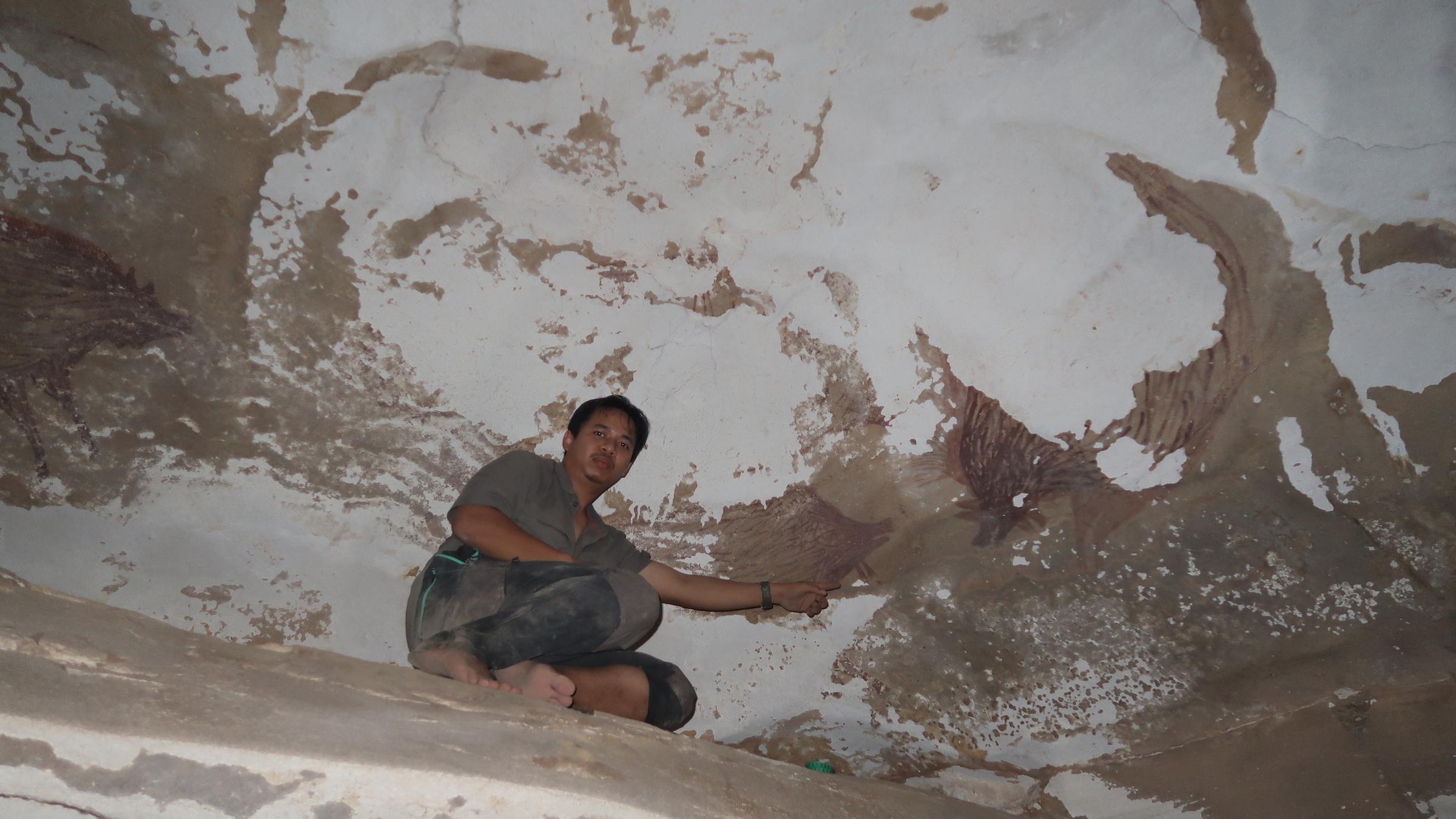 Un chercheur montre du doigt les autres porcs verruqueux sur le panneau rocheux de la grotte Leang Tedongnge.