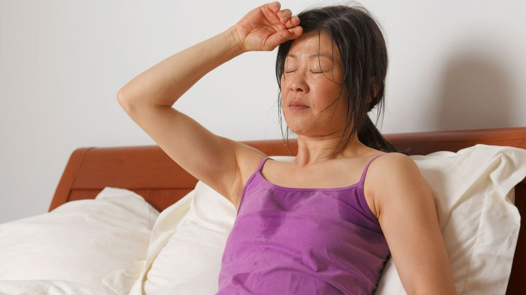 Sweaty woman sat up in bed struggling to sleep in the heat