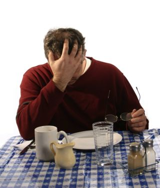 A man, upset, at a table with empty dishes.