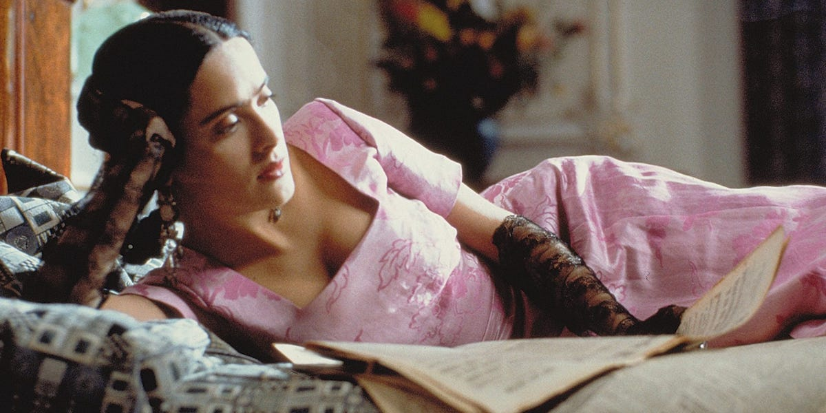 Salma Hayek as Frida Kahlo laying on a bed in Frida biopic